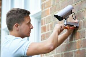 Conseiller de sécurité raccordant la caméra de sécurité au mur de la maison